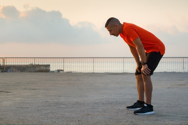 tired-male-athlete-having-break-after-jogging_1262-5912