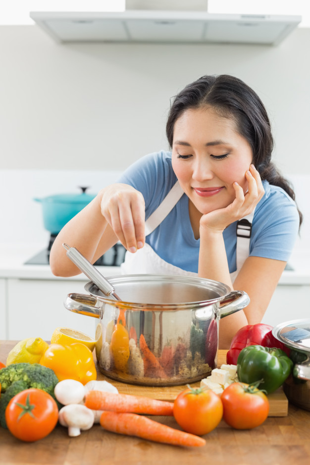 smiling-young-woman-preparing-food-in-kitchen_13339-33732