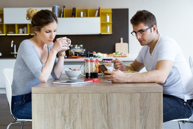 beautiful-young-couple-using-digital-tablet-and-smartphone-while-enjoying-the-breakfast_1301-5667