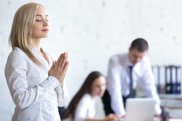 corporate-woman-meditating-at-work_1163-1611