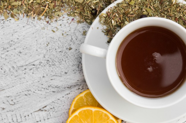 cup-with-tea-with-lemon-and-dry-herbs-on-wooden-background_1212-811