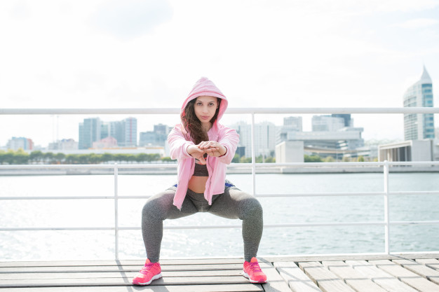 serious-sporty-woman-doing-squats-on-quay_1262-6220