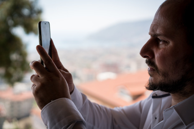 man-with-white-shirt-taking-a-photo-of-city-with-smartphone_21730-11599