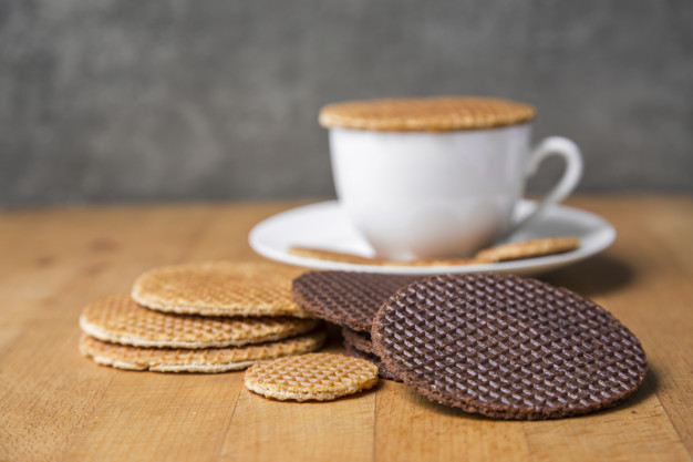 stroopwafel original Dutch dessert surve with hot coffee on wood table top  background. Stroopwafel is traditional dessert of Honland country. Stroopwafel made from syrub dough