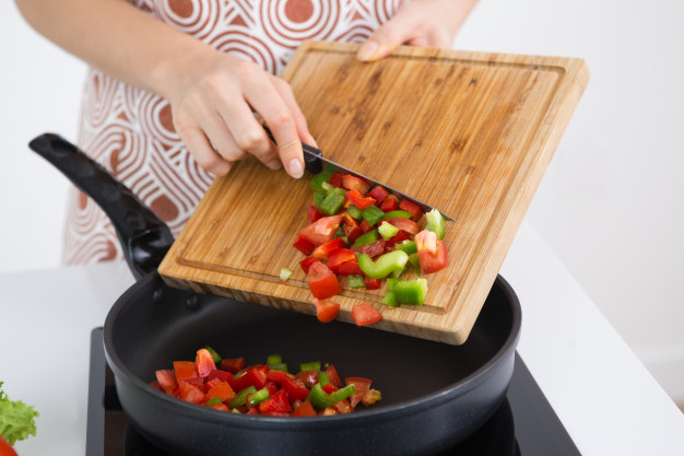 unrecognizable-woman-cooking-vegetable-stew_1262-6320