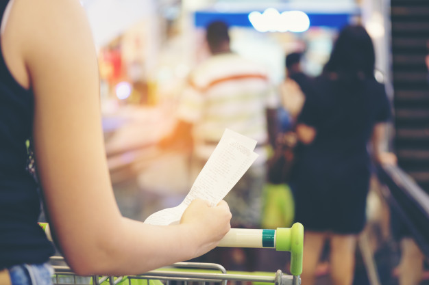 blurry-of-hand-of-woman-hold-a-bill-and-a-long-receipt-of-supermarket_28914-629
