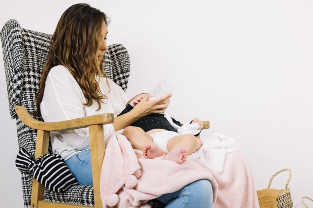 mother-feeding-baby-in-armchair_23-2147711918