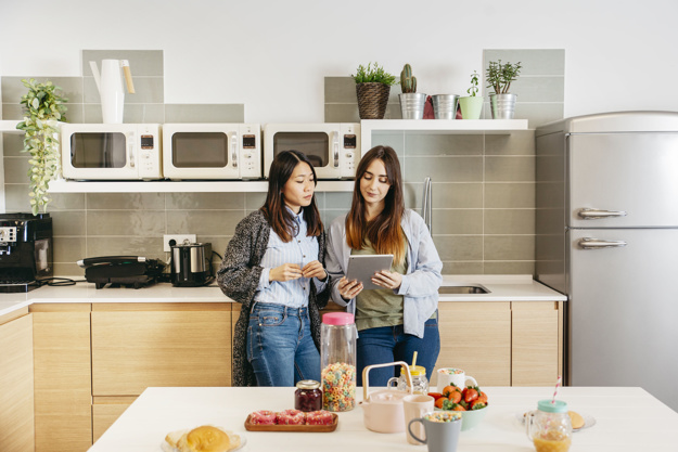 women-standing-and-watching-tablet-on-kitchen_23-2147764566