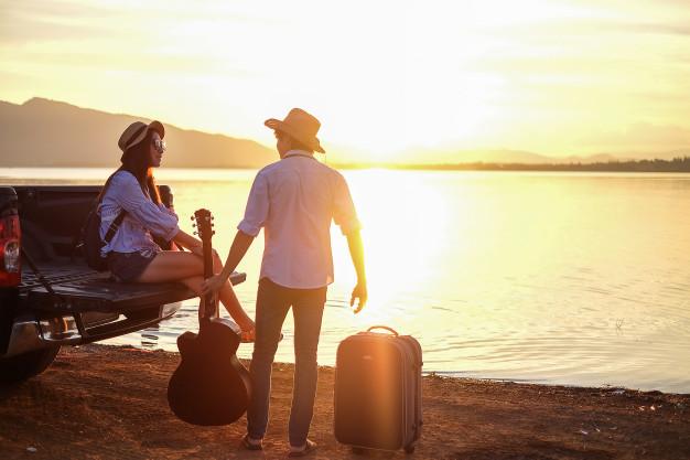 couple-traveler-playing-guitar-and-watching-sunset-near-the-lake_45381-4