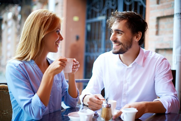 smiling-couple-drinking-coffee-and-looking-at-each-other_1098-413