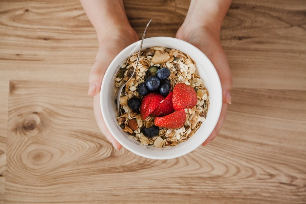 top-view-of-person-holding-muesli-bowl_23-2147666384