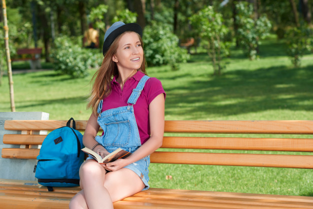 young-pretty-girl-sitting-on-the-bench-keeping-a-book_7502-407