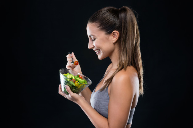 beautiful-young-woman-eating-salad-over-black-background_1301-7564