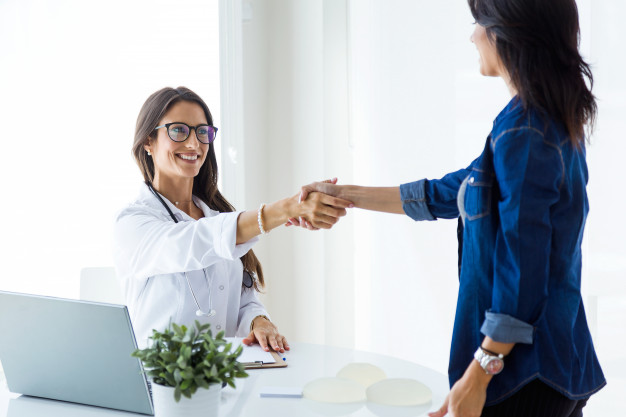 female-doctor-and-her-patient-shaking-hands-in-the-consultation_1301-7780