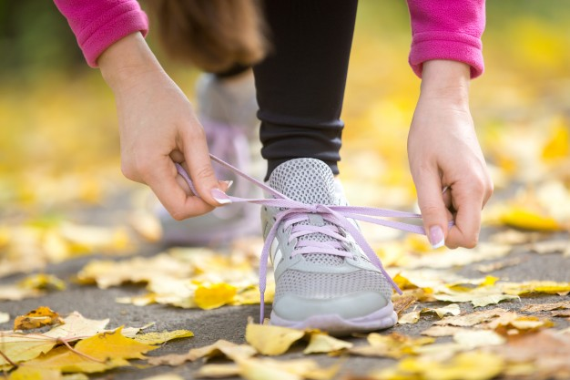 hands-tying-trainers-shoelaces-on-the-autumn-pave_1163-2702