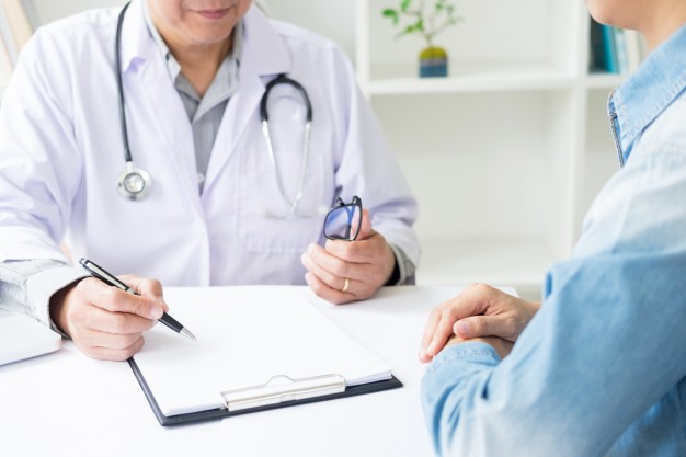 patient-listening-intently-to-a-male-doctor-explaining-patient-symptoms-or-asking-a-question-as-they-discuss-paperwork-together-in-a-consultation_1423-1367