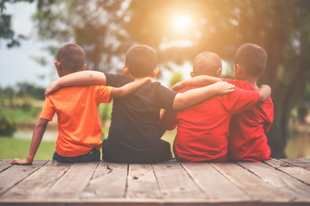 group-of-kids-friends-arm-around-sitting-together_1150-3905