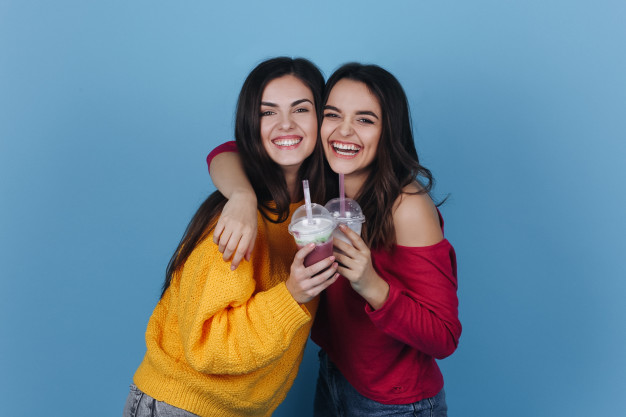 two-girls-stand-side-by-side-and-smile-while-they-drink-milkshake-and-a-cocktail_8353-5598