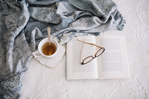 warm-tea-and-book-on-bed_23-2147711545