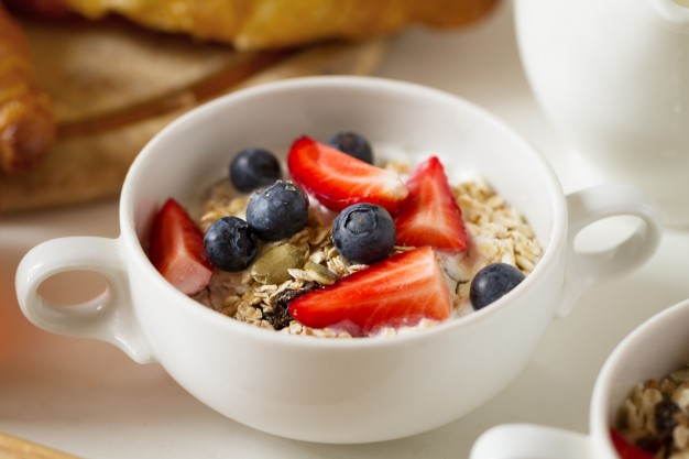 closeup-of-tasty-appetizing-muesli-with-oatmeal-fruits-yogurt-in-white-bowl-morning-healthy-food-food-concept_1220-1505