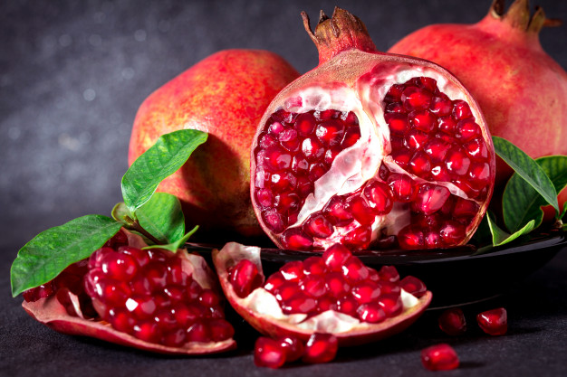 fresh-red-pomegranate-and-seed-with-leaves-over-black-stone-background_25381-173