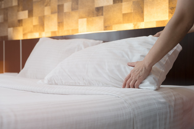 hotel-room-service-hands-set-up-white-pillow-on-the-bed-in-the-hotel_29007-752