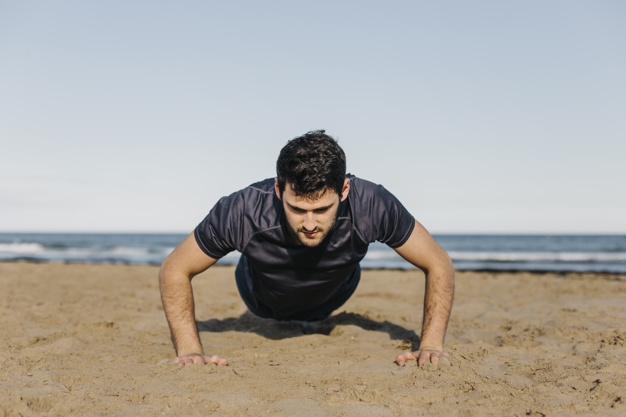 man-doing-push-ups-at-beach_23-2147802924