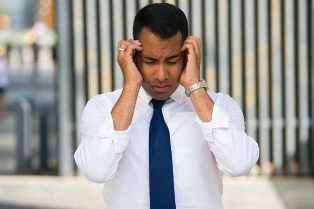 stressed-latin-businessman-holding-head-with-hands_1262-6293