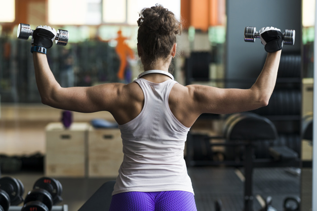 back-view-woman-exercising-with-dumbbells_23-2147789670