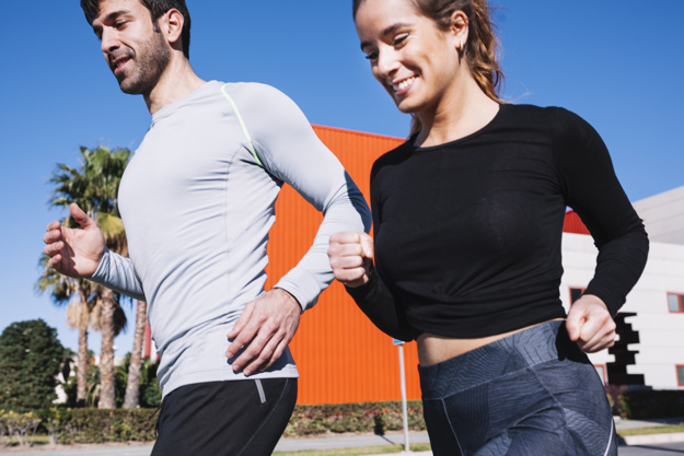 cheerful-man-and-woman-jogging-together_23-2147757970