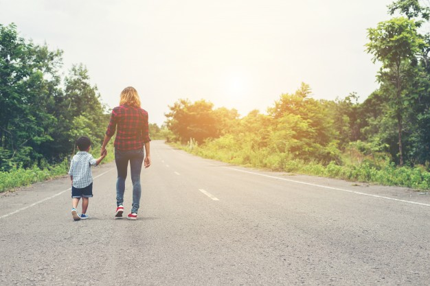 mother-holding-a-hand-of-his-son-in-summer-day-walking-on-the-st_1150-734
