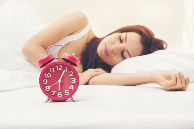 selective-focus-red-alarm-clock-in-front-of-young-girl-sleep-on-the-bed_42510-83