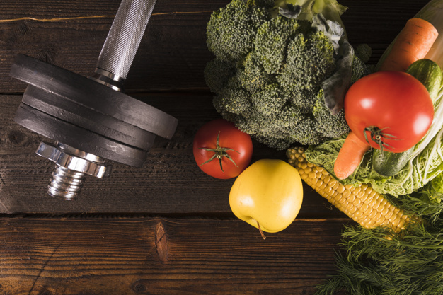 high-angle-view-of-raw-vegetables-and-dumbbells-on-wooden-background_23-2147882042