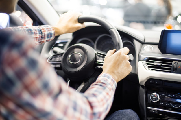 View at young handsome man driving modern car