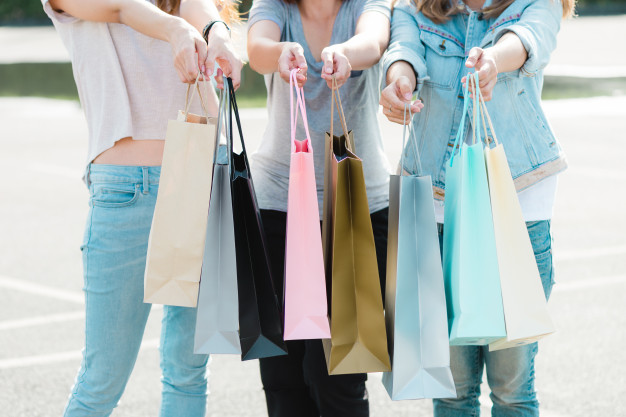 close-up-of-a-group-of-young-asian-woman-shopping-in-an-outdoor-market-with-shopping-bags_7861-1042