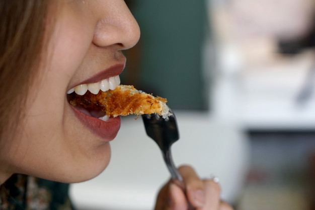 beautiful-woman-eating-croissant-with-fork-with-happiness-face_28991-97