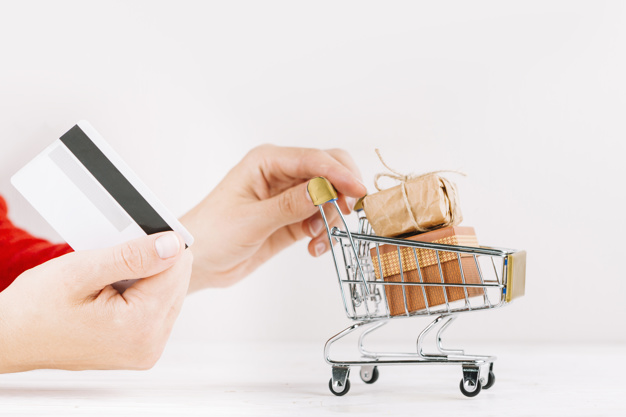 woman-holding-credit-card-and-small-grocery-cart-with-gift-boxes_23-2147950572