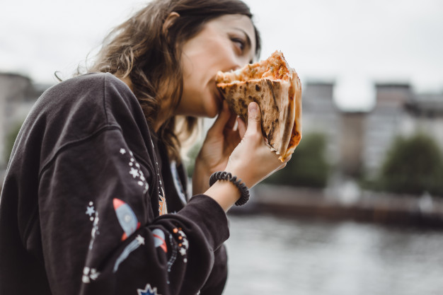 young-beautiful-woman-eating-slice-pizza-city-street_72229-268
