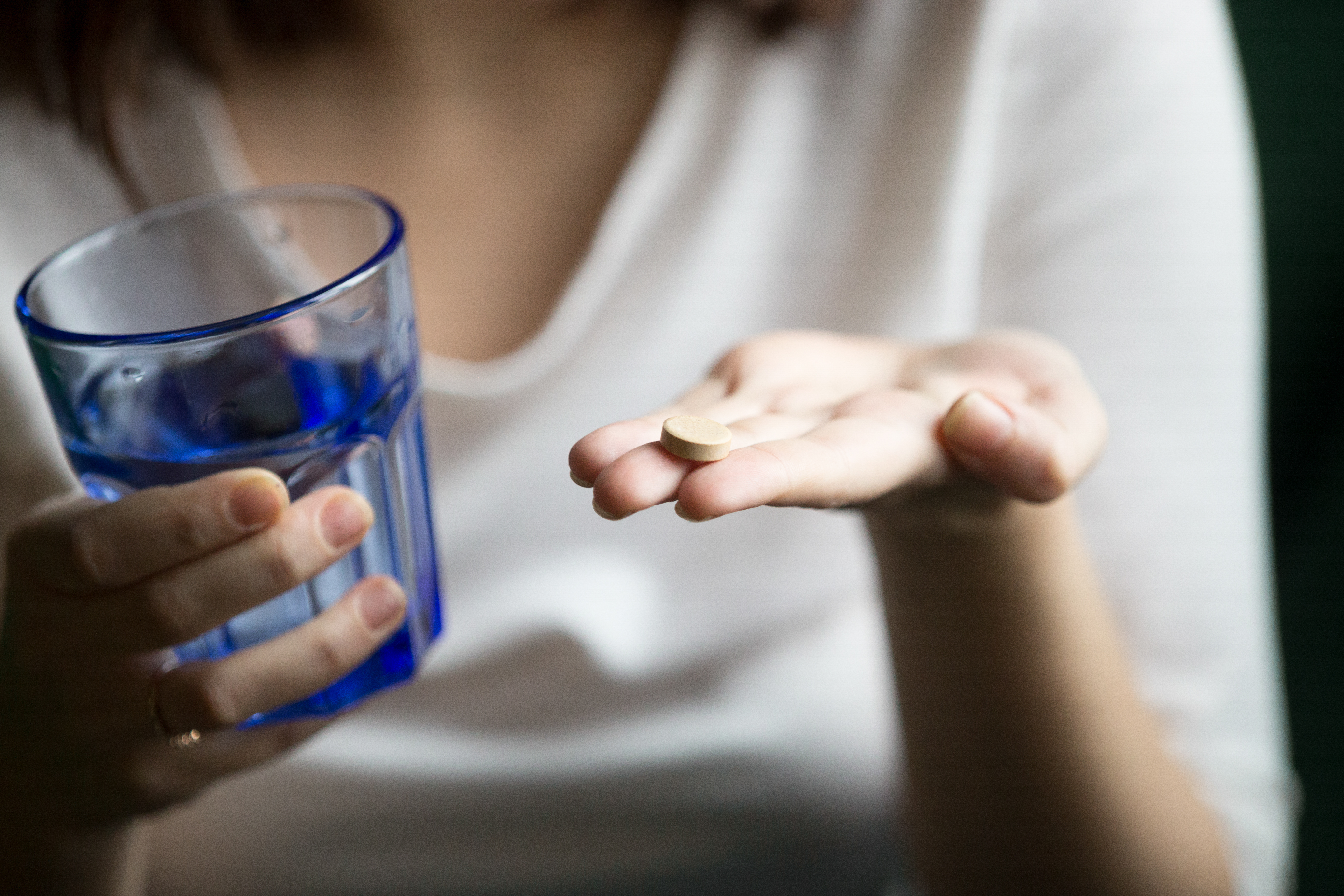 Female hands holding pill and glass of water, woman taking supplements or antibiotic antidepressant painkiller medication to relieve pain headache, contraception side effects concept, close up view