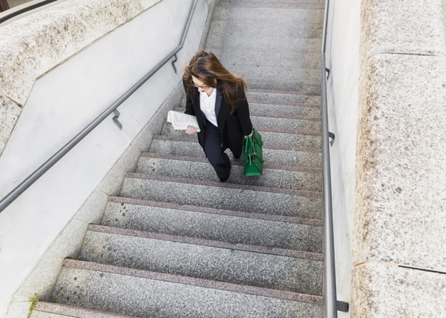 young-business-woman-with-newspaper-bag-walking-up-stairs_23-2148053686