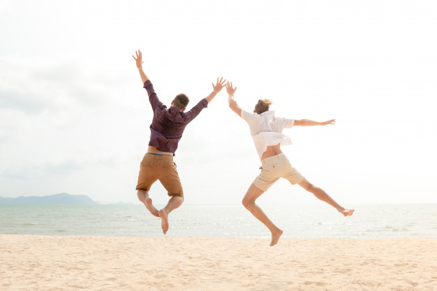 young-energetic-happy-tourist-men-jumping-beach_8087-1327